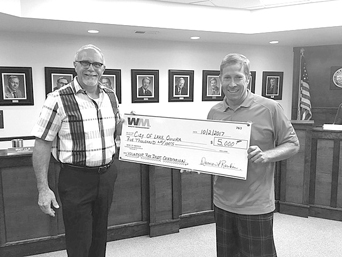Paul Howe of Waste Management (left) presents Mayor Mike Olson a $5000 donation to the Lake Quivira Fire Department. The funds will be used help fund the November 4th Fireman's Ball, honoring those who have served our community.